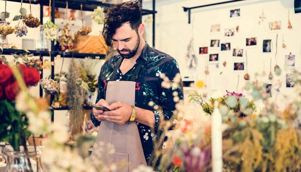 un commerçant fleuriste envoi un sms à ses clients